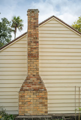 Wall of a Cottage with a Brick Chimney
