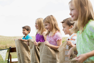 Young cousins lined up to start a potato sack race.