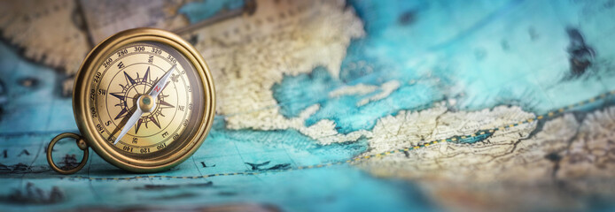 Foto op Plexiglas Noord Europa Magnetic old compass on world map.Travel, geography, navigation, tourism and exploration concept background. Macro photo. Very shallow focus.
