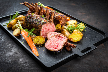 Barbecue rack of lamb with carrot and potatoes offered as closeup on a modern design cast iron tray
