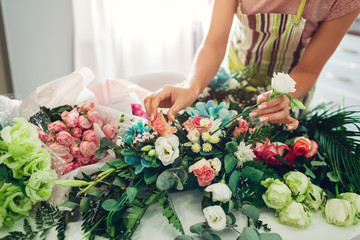 Florist woman creating flower composition at home. Worker composing bouquet for Valentines day....