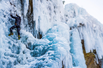 Ice Climbing Man with an Ice Axe and Crampons on a Frozen Waterfall