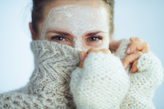 elegant woman with white facial mask hiding behind clothes