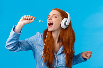 Passionate and carefree cute foxy european redhead woman in pyjama, close eyes wearing headphones,...