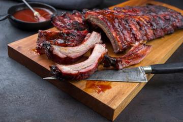 Barbecue Schweine Spare Ribs  St Louis cut mit scharfer Honig Chili Marinade als closeup auf einem Modern Design Holz Board