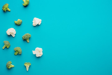 Composition of broccoli and cauliflower on a mint color paper background. Pastel.