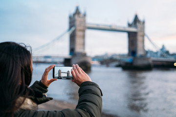 Woman taking a photo with the smart phone to the Tower Bridge in London on a sunny winter day, London, Great Britain.