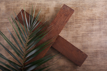 Wall Mural - Palm Sunday. Palm brunch on wooden background with cross. Easter