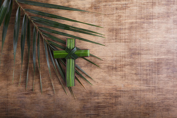 Palm sunday concept: Cross shape of palm branch on an antique wooden background