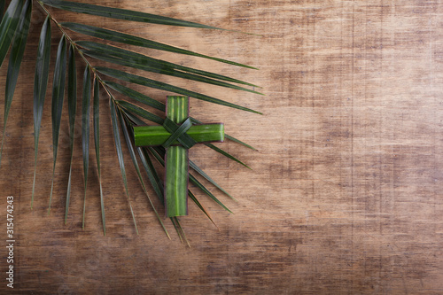Wall mural Palm sunday concept: Cross shape of palm branch on an antique wooden background