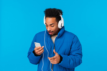 Excited and amused, happy smiling african-american man seeing favorite artist uploaded new song,...