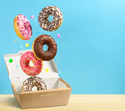Donuts falling in paper box on blue background. Copy space