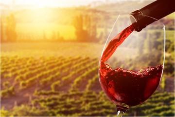 Spoed Foto op Canvas Wijn Red wine being poured in wineglass on background