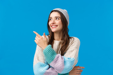 Happy charismatic, friendly young hipster girl in winter hat, sweater, pointing looking upper left...