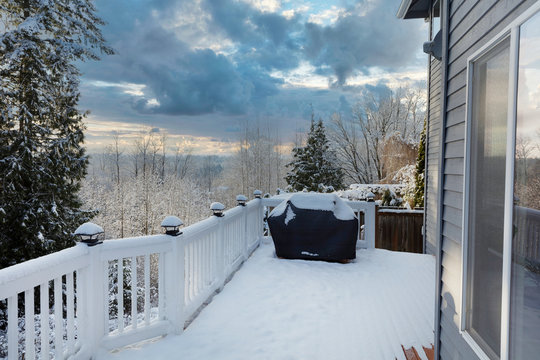 Home outdoor deck closed for the winter with snow on BBQ cooker cover