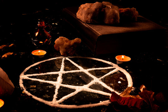 Pentagram made of salt, a pagan symbol used for protection by the wiccan community,  surrounded by candles, herbs and spices on a black shiny table top.