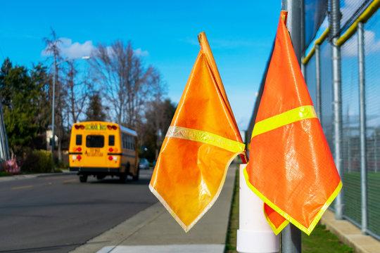 Bright orange pedestrian crossing flags at a crosswalk near school. Blurred school bus in background