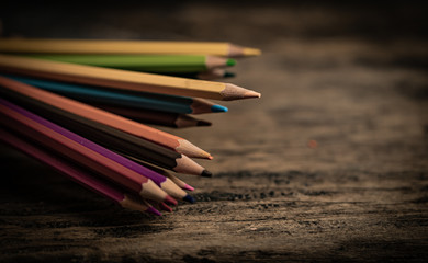 Arrangement of colored pencils on a dark brown wooden table. Cinematic concept to keep on being creative and a way to motivate children to continue their education.
