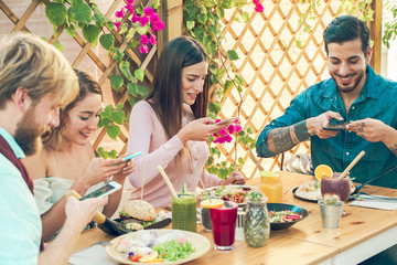 Young people Making photos to the food and smoothie bowls. Happy friends having a healthy lunch in restaurant outdoor. Food and drink trends concept - Image