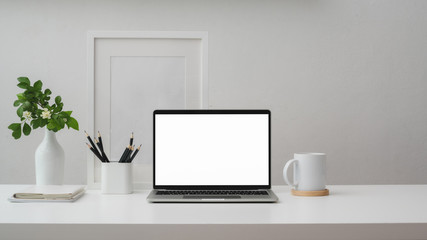 Wall Mural - Cropped shot of workspace with blank screen laptop, frame, pencils, coffee cup and vase on white table with white wall