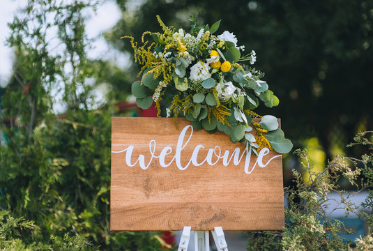 Wedding decorations. Wooden plate with fresh flowers for of events with inscription - Welcom. Board made of wood for information and congratulations at the ceremony. Copy space, mockup.