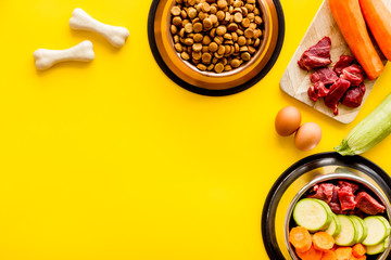 Dog feed - dry food and raw meat - near cheving bones on yellow background top view copy space