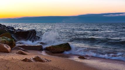 Wave crashing on the rocky seashore at sunset time
