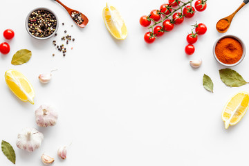 Kitchen frame with spices and food - pepper, garlic, cherry tomatoes - on white background top-down frame copy space