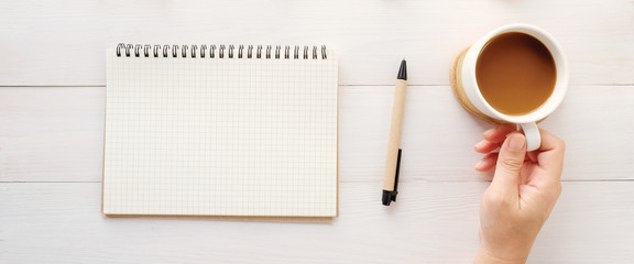 Blank note book paper, pen and hand holding a coffee cup on white table desk office, Business,...