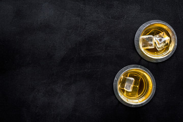 Photo sur Plexiglas Bar Whiskey with ice. To glasses of strong alcohol drink on black desk top-down frame copy space