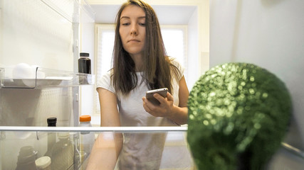 woman at fridge with smartphone making list of necessary food at home kitchen. Smart shopping list