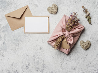 Zero waste Valentine's Day concept and mock up. Eco-friendly gift cloth wrapping in Furoshiki style, craft paper envelope, empty gift or greetings card, copy space