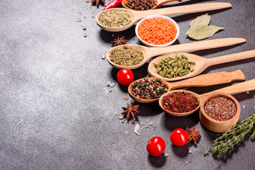 A set of spices and herbs. Indian cuisine. Pepper, salt, paprika, basil and other on a dark...