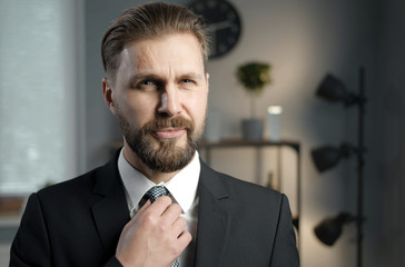 Bearded mature businessman in black formal suit fixing his check necktie looking at camera