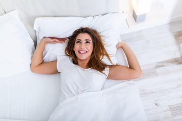 Image of young smiling pretty lady lies in bed indoors. Eyes closed. Waking up concept Beautiful...