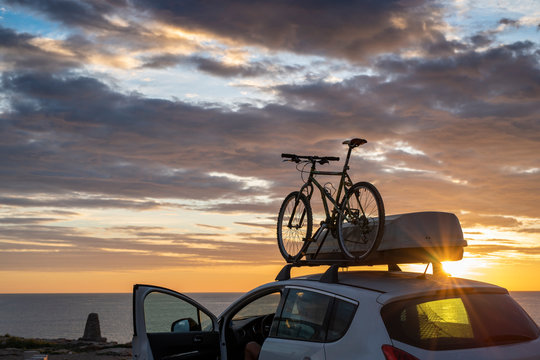 Mounted mountain bicycle silhouette on the car roof with evening sun light rays background. Safe sport items transportation using a car concept image.