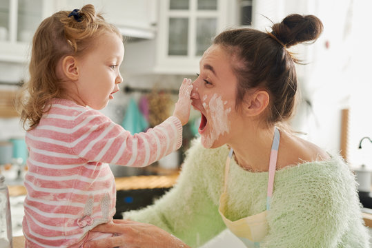 Mum and her little daughter playing with flour in kitchen