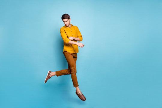 Full length profile photo of funny guy jumping high visiting shopping mall fixing clothes metrosexual wear yellow shirt pants isolated blue color background