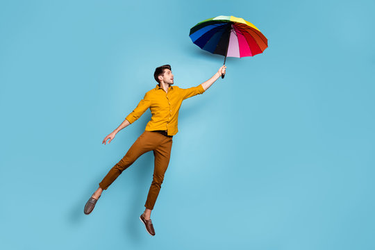 Full length photo of crazy guy jumping high holding colored bright umbrella flying up higher wear yellow shirt trousers isolated blue color background