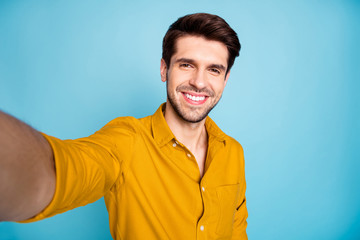 Closeup photo of freelancer business guy making selfies for social blog post excited positive weekend mood wear yellow shirt isolated blue color background