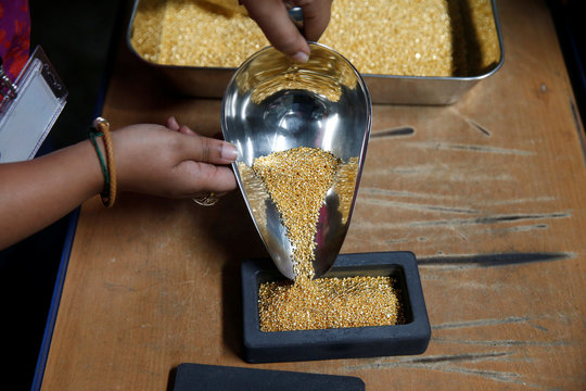 An employee pours gold grain to make a 1kg gold bar during a refining process at AGR (African Gold Refinery) in Entebbe