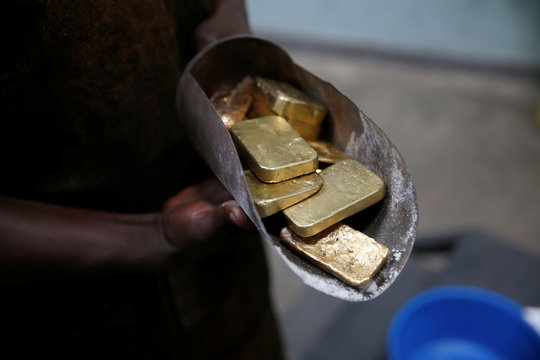 An employee holds gold bars before the refining process at AGR (African Gold Refinery) in Entebbe