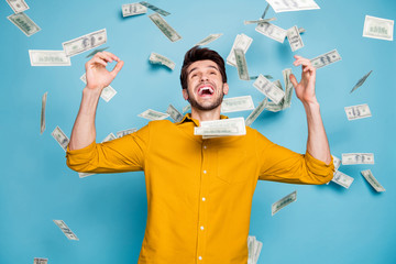 Photo of screaming excited emotional guy having won jackpot in lottery smiling toothily isolated over blue pastel color background in yellow shirt