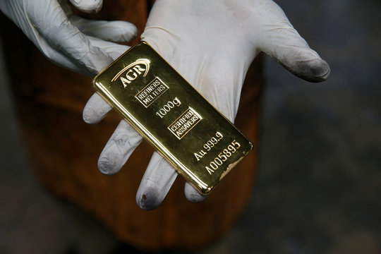 An employee holds a 1kg gold bar at AGR (African Gold Refinery) in Entebbe