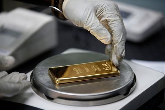 An employee weighs a 1kg gold bar at AGR (African Gold Refinery) in Entebbe