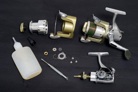 A fishing spinning reel as a whole and a second similar completely disassembled on a dark wooden background. Top view.