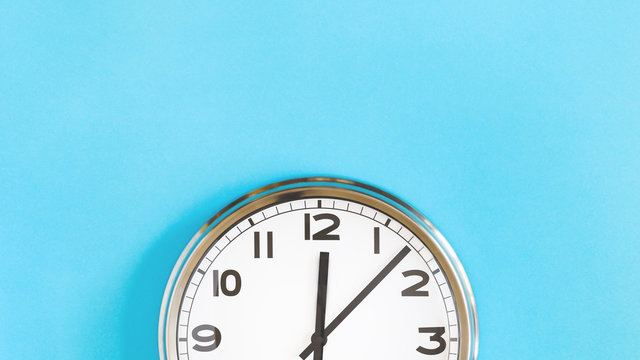 Top of big plain wall clock on pastel blue background. Five past twelve o'clock. Top view copy space, time management or school concept and summer or winter time change, opening hours, lunch break