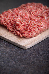 Minced Meat (Beef) as detailed close-up shot on dark background
