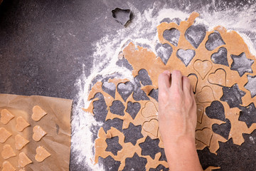 Rolled dough on a kitchen counter with cut out shapes while baking cookies or biscuits