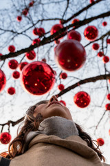 beautiful woman under a tree with red balls